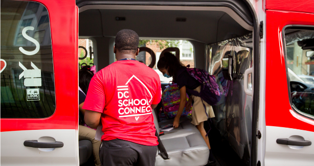 Picture of a man in a DC School Connect t-shirt helping a young child get into a School Connect van.